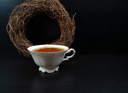 Hot tea cup porselain with wicker wreath at black wooden background
