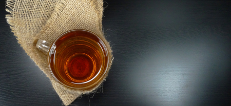Hot tea cup on a winter day with burlap / hessian at a black background / tea time! 免版税图像