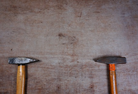 Hammers on a wooden board background