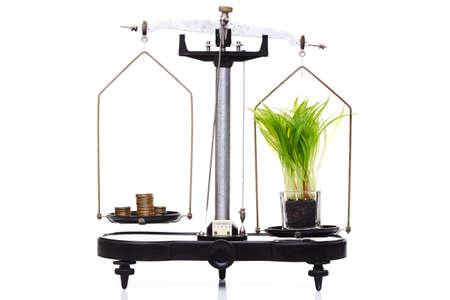 balanza de laboratorio: el concepto de medio ambiente, ecología, tecnología verde. contrapesos de equilibrado aislados en blanco, el dinero vale más que la tierra Foto de archivo