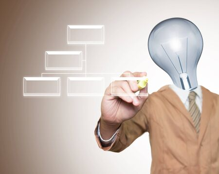 Young businessman with lamp-head and marker writting light box on screen photo