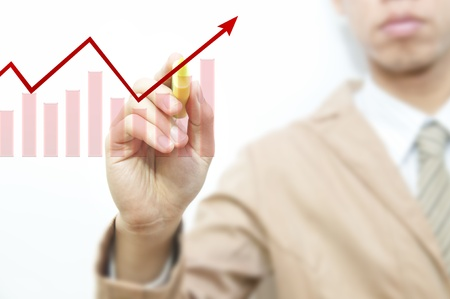 Young business man drawing red graph and chart, isolated over white background  photo