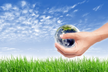 Hand with earth globe on green grass landscape background, ecology concept photo