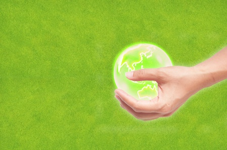 Hand with earth globe on green grass background, ecology concept photo