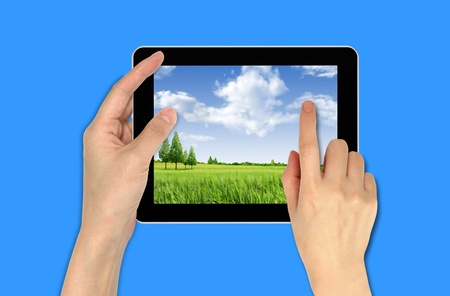 a male hand holding a touchpad with landscape wallpaper photo