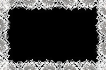 crochet: White lace pattern isolated on  a delicate border against black background.