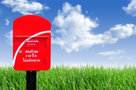 Red thailand post box on green grass and blue sky background photo