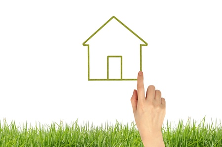 The House and hands with green grass as a symbol of the real estate business.  Stock Photo - 10430144