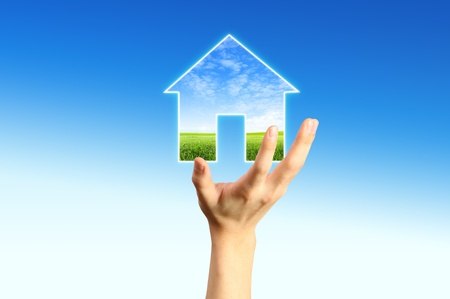 property insurance: The House and hands with blue sky as a symbol of the real estate business.  Stock Photo