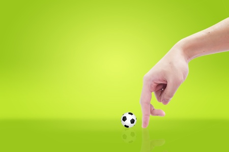 finger and soccer ball on green grass background photo