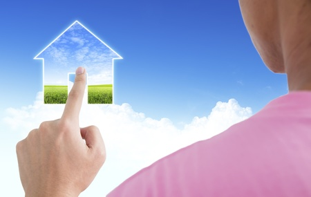 Man point finger on the screen with blue sky as a symbol of the real estate business photo