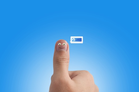 Smiling cartoon face on human thumb up on background Stock Photo - 10473271