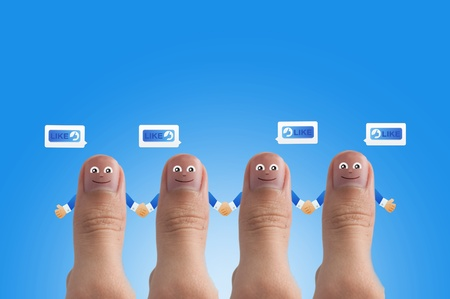 Smiling cartoon face on human thumb up on background photo