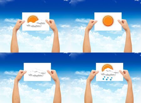 Hand holding a paper with weather sign on landscape blue sky background photo