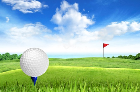 golf field: Golf ball on tee off with sea view over the blue sky background  Stock Photo