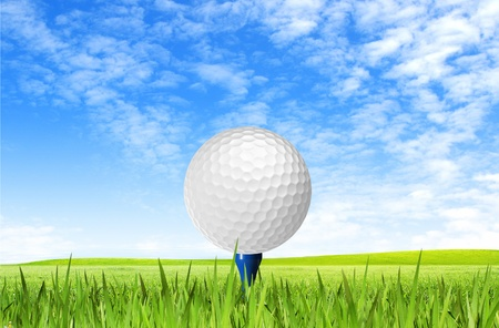 tee off: Golf ball on tee off over the green grass and clouded sky Stock Photo