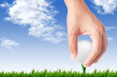 cut up: Hand drop golf ball on tee off with blue sky background