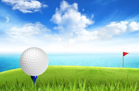tee off: Golf ball on tee off with sea view over the blue sky background  Stock Photo