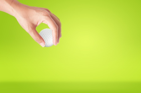 cut up: Close-up of hand holding golf ball with green grass for web design background