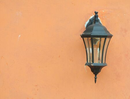 Old street lantern hanging on the orange wall photo