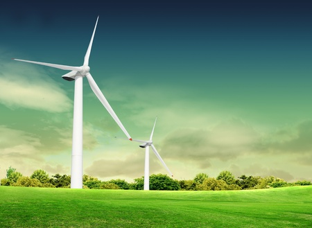 Wind turbine on the green grass over the blue clouded sky photo