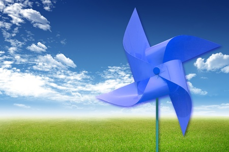 Colorful windmaill toy on the green grass and blue sky background, for ecology idea and concept photo