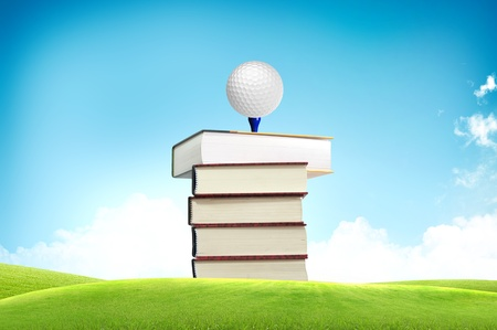 Golf ball on book tee off with green grass field over the blue sky background  photo
