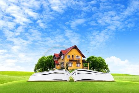 cielos abiertos: Libro y casa amarilla enel medio del bosque verde para viajar y eco-concepto Foto de archivo