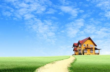 De weg naar huis op groen veld landschap met blauwe hemel Stockfoto