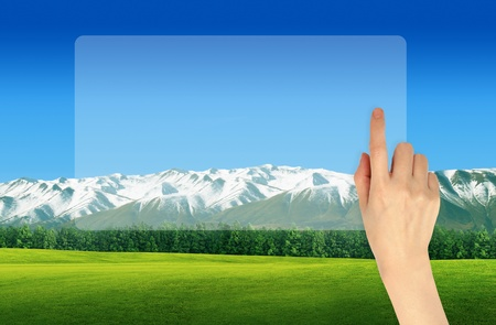 Hand with digital screen with landscape background photo