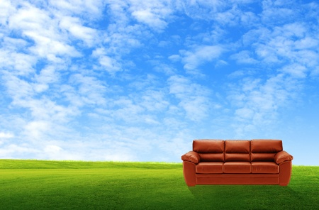 lawn chair: Red sofa on a green landscape