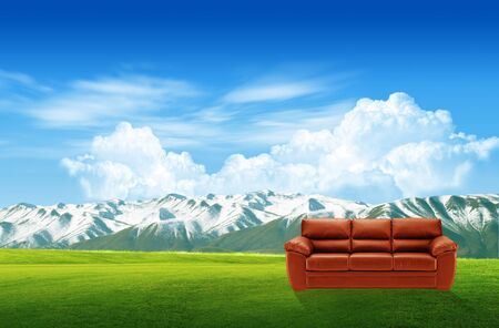 Red sofa on a green landscape photo