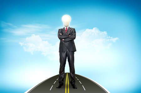 A business man bulb standing over road and blue sky the background photo