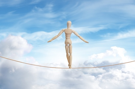 crisis management: Wooden model standing on a rope over the cloud sky