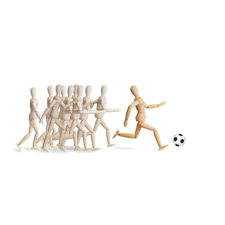 wooden mannequin: Wood puppet playing soccer with ball isolated over white background