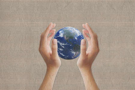 Hand showing earth on texture recycled paper background photo