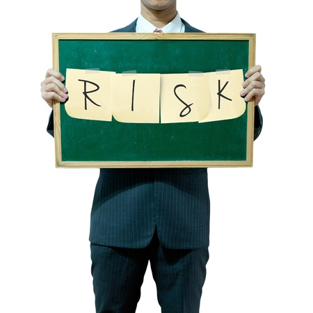 Business man holding board on the background, RISK Stock Photo - 15559802