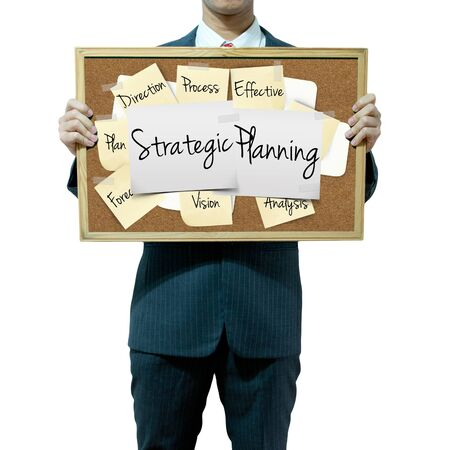 stratgy: Business man holding board on the background, Strategic Planning concept Stock Photo
