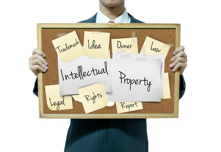 intellectual property: Business man holding board on the background, intellectual property