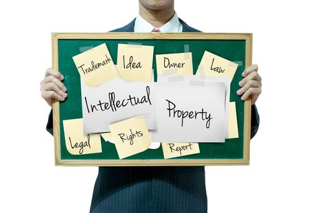 property rights: Business man holding board on the background, intellectual property