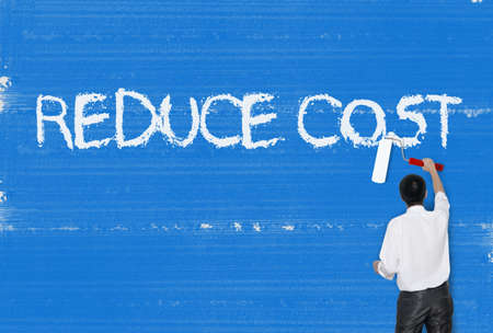 cost reduction: Man painting word on cement texture wall background, Cost reduction Stock Photo