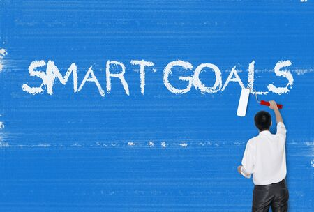 achievable: Man painting word on cement texture wall background, Smart Goals Stock Photo