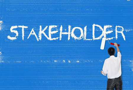 Man painting word on cement texture wall background, Stakeholder Stock Photo - 17049206