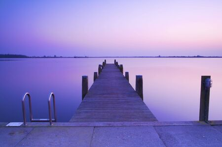 a beautiful blue sunset with a jetty over a lake with an evening glow