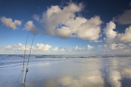 Two fishing rods at the beach in summer with a blue sky and white clouds