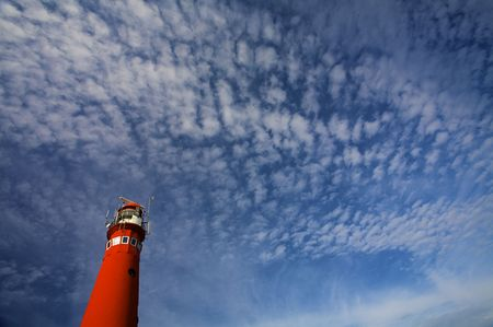 a classic red lighthouse against a cloudy blue sky in summertime