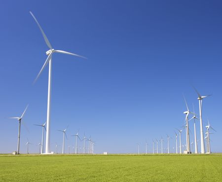wind turbines farm in a green field producing energy
