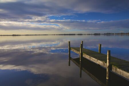 Landscape in Holland with a calm lake and sunset wit a jetty