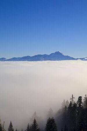 Hoch in den Bergen der Alpen in Österreich über den Wolken mit einem blauen Himmel Standard-Bild