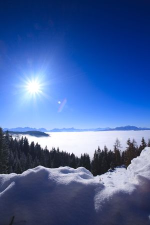High in the mountains of the Alps in Austria above the clouds with a blue sky